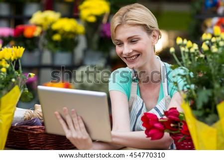Happy female florist using digital tablet in florist shop - stock photo