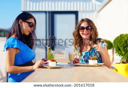 happy female friends enjoying cakes in cafe, pregnant women - stock photo