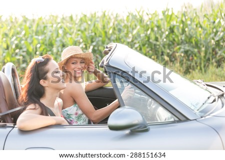 Happy female friends enjoying road trip in convertible - stock photo