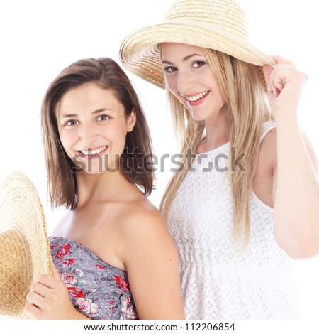 Happy female friends enjoying the summer in their casual  dresses and straw sunhats - stock photo
