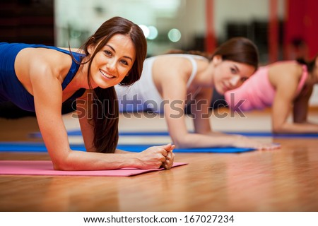 Happy female friends exercising and having fun in a gym class - stock photo