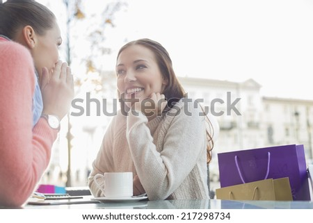 Happy female friends gossiping at outdoor cafe - stock photo