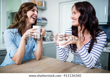 Happy female friends holding coffee mugs while discussing at table in kitchen - stock photo