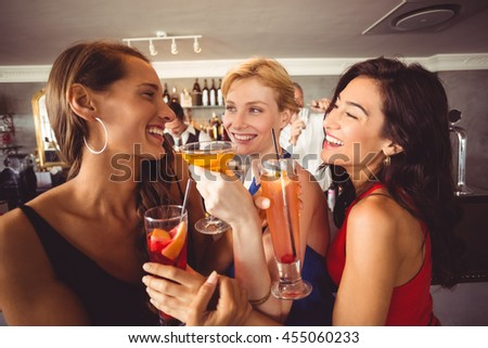 Happy female friends holding glass of cocktail in restaurant