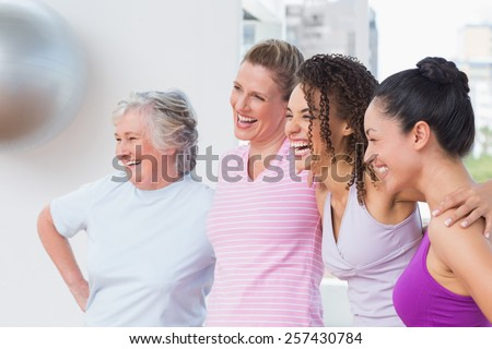 Happy female friends standing arms around in fitness studio - stock photo