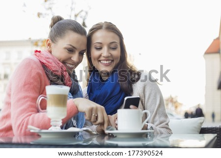 Happy female friends using cell phone at sidewalk cafe - stock photo