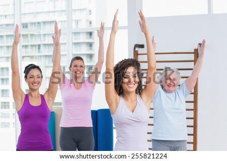 Happy female friends with arms raised exercising in gym - stock photo