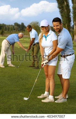 Happy female golfer learning to play.