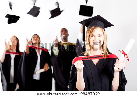 happy female graduate at graduation with classmates throwing caps in background