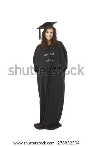 Happy female graduate standing in full academic dress, smiling. - stock photo