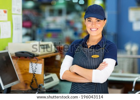 happy female hardware store cashier with arms folded - stock photo