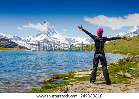 Happy female hiker among the mountains. European Alps. Swiss. Matterhorn view  - stock photo