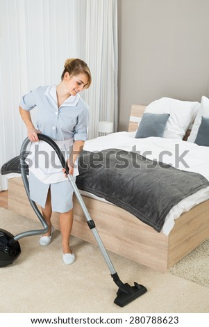 Happy Female Housekeeper Cleaning Floor With Vacuum Cleaner In Hotel Room