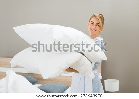Happy Female Housekeeping Worker With Pillows In Hotel Room - stock photo
