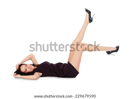 Happy female in black dress lie on the floor - stock photo