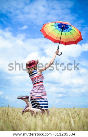 Happy female in stripped dress and red hat jumping with rainbow umbrella in the wheat field on sunny blue sky outdoors background