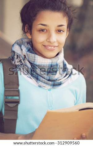 Happy female indian student with book - stock photo
