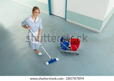 Happy Female Janitor With Mop And Cleaning Equipment On Floor