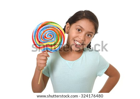 happy female latin child holding big lollipop candy in cheerful face expression in sugar addiction and kid love for sweet concept isolated on white background - stock photo