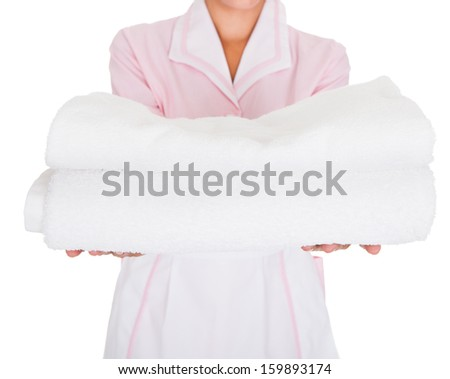 Happy Female Maid Holding Stack Of White Towels Over White Background - stock photo