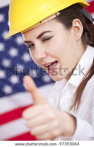 happy female manual worker with thumb up sign over american flag