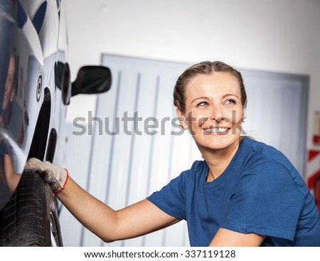Happy female mechanic looking away while fixing car tire at auto repair shop - stock photo
