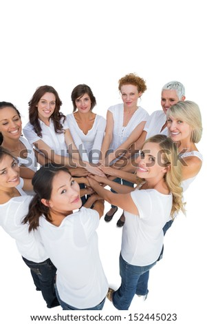 Happy female models joining hands in a circle and looking at camera on white background