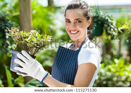 happy female nursery worker in greenhouse - stock photo