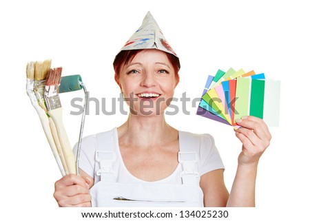Happy female painter with color samples and brushes - stock photo