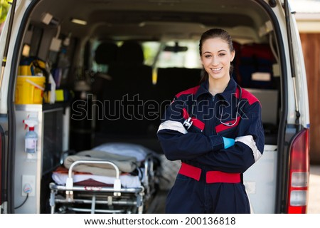 happy female paramedic standing in front of ambulance - stock photo