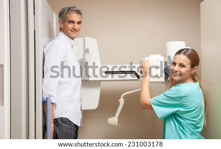 Happy female patient in 40s undergoing x-ray scan. Health concept. - stock photo