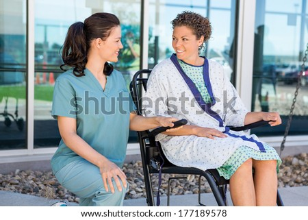 Happy female patient looking at nurse while sitting on wheelchair at hospital courtyard - stock photo