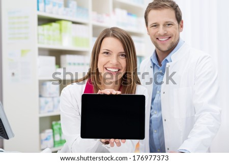 Happy female pharmacist doing a promotion displaying the blank screen of a tablet-pc to the camera as she stands in the pharmacy with a male colleague