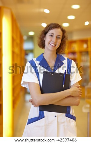 Happy female pharmacist with clipboard in pharmacy