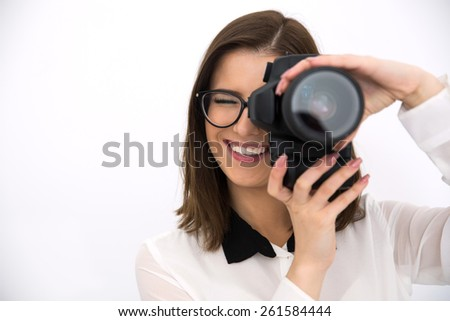 Happy female photographer with camera over gray background - stock photo