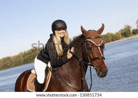 Happy female rider leaning over horse caressing back at riverside. - stock photo