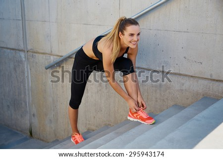Happy female runner tying shoelaces on stairs - stock photo