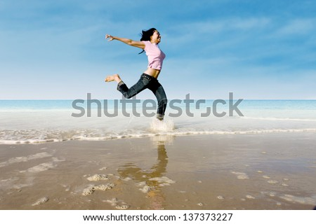 Happy female running around on the beach