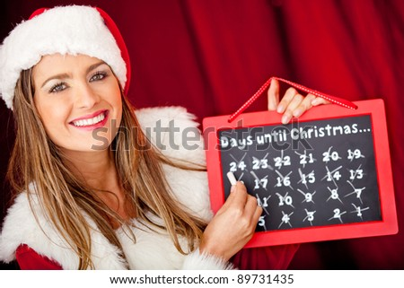 Happy female Santa counting the days for Christmas on a board