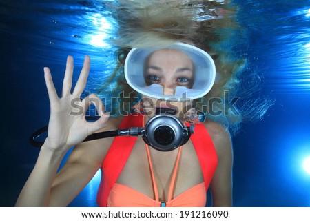 Happy female scuba diver show underwater signal  - stock photo