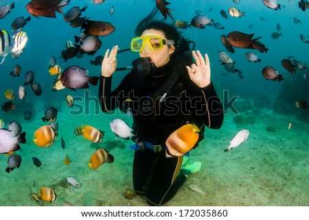 Happy female SCUBA diver surrounded by tropical fish - stock photo