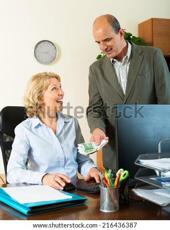 Happy female secretary receiving from boss salary in cash