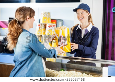 Happy female seller giving popcorn paperbag to pregnant woman at cinema concession stand - stock photo