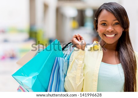 Happy female shopper at the shopping center smiling