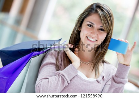 Happy female shopper holding a credit card and smiling - stock photo