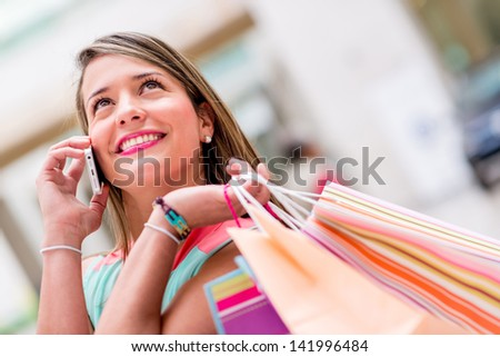 Happy female shopper talking on the phone and smiling