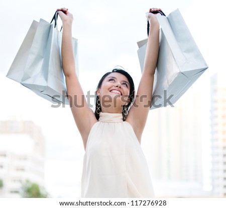 Happy female shopper with arms up holding shopping bags - stock photo