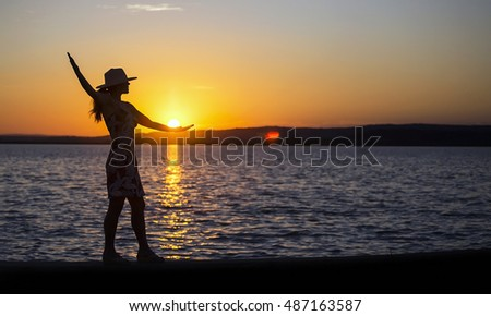 Happy female silhouette at sunset on the beach