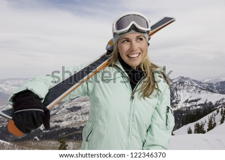 Happy female skier with skis standing at snowy landscape