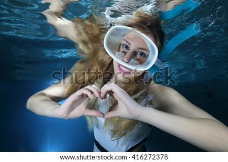 Happy female snorkeler show underwater heart signal  - stock photo